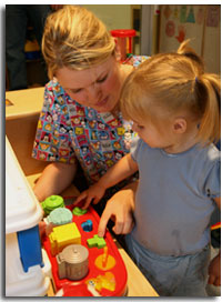A nurse with a child playing with shape blocks
